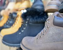 Winter boots display for sale in clothing store. Image of a Royalty Free Stock Images