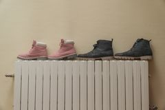 Winter boots are dried on the battery near the wall.  Royalty Free Stock Photos