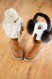 Winter boots, hat and fur headphones on the floor vertical Stock Photography