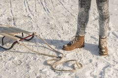 Winter boots on snow near sledge with rope. royalty free stock photos