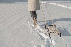 Winter boots on snow near sledge with rope. royalty free stock image