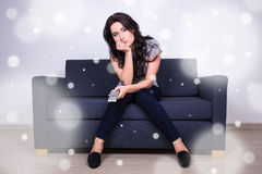 Winter boredom - young bored woman sitting on sofa and watching Royalty Free Stock Photography