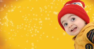 Winter Boy on Bright Yellow Snowflake Background. Stock Photo