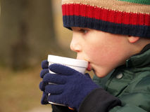 Winter boy drinking cocoa royalty free stock photography