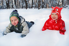 Winter boy with a girl lying in the snow in the forest Royalty Free Stock Photo