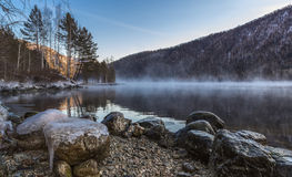 Winter breath of the Yenisei River. Morning. A light mist on the Yenisei. The stones are covered with ice. Sayan. Khakassia. Siberia Royalty Free Stock Image