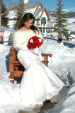Winter Bride. Beautiful bride outside sitting on a bench in the snow royalty free stock photos