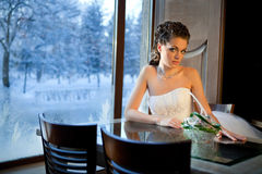 Winter Bride Sitting near the window. Beautiful Bride Sitting near the window in the Wonderful Winter Evening Stock Photos