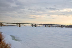 Winter bridge. Bridge over the river covered with ice Stock Photography