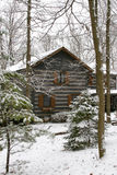 Winter cabin. A log cabin in a snow covered wooded area Royalty Free Stock Image