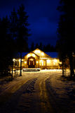 Winter Cabin Glowing Warm at Night Blue Sky Royalty Free Stock Photos
