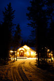 Winter Cabin at Night with Snow and Warm Glowing Lights Stock Photos