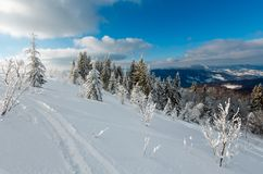Winter mountain snowy landscape. Winter calm mountain landscape with beautiful frosting trees and ski track through snowdrifts on mountain slope Carpathian Stock Photo
