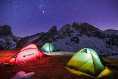 Winter camp, night, shining green tent in the snow. Night shot, long exposure, sleeping in the snow outside. Alps mountains royalty free stock photo