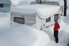 Winter camping. Snow-covered camping caravan during tough winter Royalty Free Stock Image