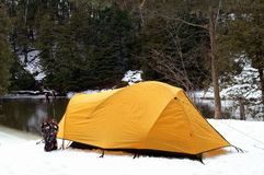 Winter Camping. Backcountry snowshoeing in January typically delivers much colder weather! An Ontario river flowing free of ice is an ideal place to make camp Stock Photo