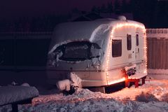 Winter camping holiday. Decorated garland. white Caravan Stock Photo