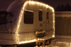 Winter camping holiday. Decorated garland. white Caravan Royalty Free Stock Image