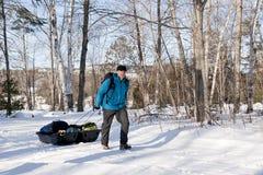 Winter Camping - Killarney Provincial Park, ON. An active man pulls a toboggan along a snowy track to a camping yurt in Killarney Provincial Park, Ontario Royalty Free Stock Photos