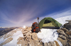 Winter camping in the mountains with a backpack and tent. Camping on the top of the mountain in winter Royalty Free Stock Photo