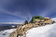 Winter camping in the mountains with a backpack and tent. Camping on the top of the mountain in winter Stock Photo