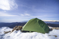 Winter camping in the mountains with a backpack and tent. Camping on the top of the mountain in winter Royalty Free Stock Photos