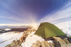 Winter camping in the mountains with a backpack and tent. Camping on the top of the mountain in winter Royalty Free Stock Image