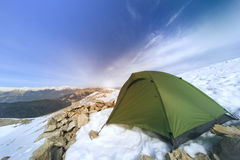 Winter camping in the mountains with a backpack and tent. Camping on the top of the mountain in winter Stock Image