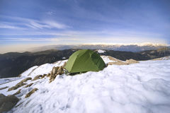 Winter camping in the mountains with a backpack and tent. Camping on the top of the mountain in winter Stock Photography