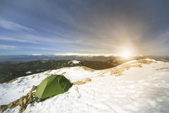 Winter camping in the mountains with a backpack and tent. Camping on the top of the mountain in winter Royalty Free Stock Images