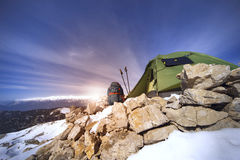 Winter camping in the mountains with a backpack and tent. Camping on the top of the mountain in winter Stock Images