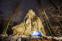 Winter camping in the mountains. Night photography. Winter camping. Blue tent in a mountain forest next to amazing light painting rocky boulder. Night Royalty Free Stock Photography
