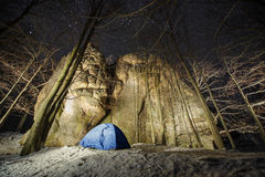 Winter camping in the mountains. Night photography. Winter camping in the mountains. Blue tent in a mountain forest next to amazing light painting rocky boulders Stock Image