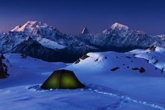 Winter camping, night, shining green tent on snow. Night shot, long exposure, sleeping on snow in the outdoors. Alps Mountains royalty free stock photography