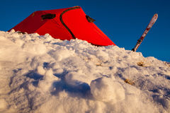 Winter camping. Red tent set on a snow slope Stock Image