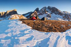 Winter camping, shining green tent on snow. sleeping on snow in the outdoors. Alps Mountains stock image