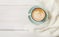 Winter cappuccino coffee cup on white wood background. Winter cappuccino composition. Blue coffee cup top view with foam and knitted sweater at white wood stock image