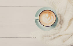 Winter cappuccino coffee cup on white wood background. Winter cappuccino composition. Blue coffee cup top view with foam and knitted sweater at white wood stock images