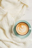 Winter cappuccino coffee cup on white wood background. Winter cappuccino composition. Blue coffee cup top view with foam and knitted sweater at white wood royalty free stock photos