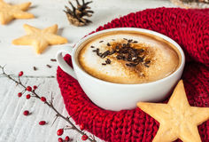 Winter cappuccino coffee in white cup with christmas cookies. Winter cappuccino coffee in a white cup with star shaped christmas cookies and warm scarf - red and Royalty Free Stock Photos