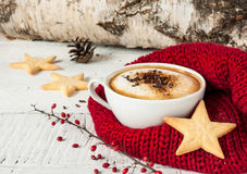 Winter cappuccino coffee in white cup with christmas cookies. Winter cappuccino coffee in a white cup with star shaped christmas cookies and warm scarf - red and