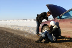 Winter Car Breakdown. A couple are stranded at side of highway with a car breakdown in winter royalty free stock images