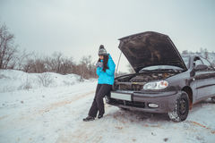 Winter car breakdown - woman call for help, road assistance stock photo