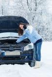 Winter car breakdown - woman try to repair motor. Stock Photography