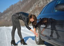 Winter car breakdown - young fashion woman trying to fix the car Stock Photo