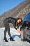 Winter car breakdown - young fashion woman trying to fix the car Royalty Free Stock Photo