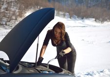 Winter car breakdown - young fashion woman trying to fix the car Stock Image