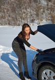 Winter car breakdown - young fashion woman trying to fix the car Stock Photography