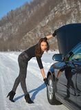 Winter car breakdown - young fashion woman trying to fix the car Stock Images