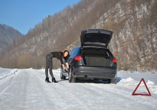 Young fashion woman trying to fix the car. Winter car breakdown - young fashion woman trying to fix the car Royalty Free Stock Photography
